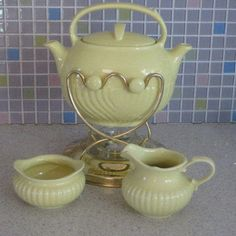 This is a really nice vintage pottery teapot set manufactured by Hall for the Forman family. The set includes the dual spout tip pot design teapot in yellow with a matching open sugar and creamer as well as the brass tone metal stand with candle warmer. The pieces are all in excellent condition with no chips,cracks or damage,and appear to have never been used. The warming stand is also in very nice condition. The teapot measures about 9 inches wide from spout to spout and is about 7 1/4 ...