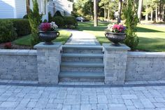 stone walls landscaping I like the idea of putting flower pots on the stone-pillars Backyard Retaining Walls, Sloped Backyard, Backyard Patio Designs, Retaining Wall With Steps, Concrete Patio, Shade Landscaping, Front Yard Landscaping, Luxury Landscaping, Landscaping Ideas