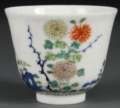 A FINE CHINESE QING DYNASTY EGG SHELL PORCELAIN DOUCAI WINE CUP, Kangxi mark and of the period. Of tapering cylindrical form raised on a short circular foot, finely decorated with enameled chrysanthemum blossoms and underglaze blue. Inscription on verso, six character mark in underglaze blue within double circles. Diameter 2.5 inches (6.5 cm), height 2 inches (5.2 cm). Sold for $30,000