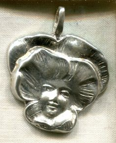 Sterling pansy charm with woman's face.