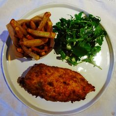 Chicken Kiev with a garlic tarragon & parsley butter, served with dressed rocket salad & jacket fries.