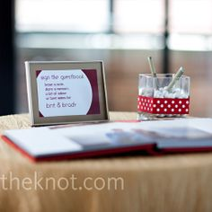 Pens for the photobook were placed in a square vase holding white gumballs and accented with a red-and-white polka-dot ribbon.