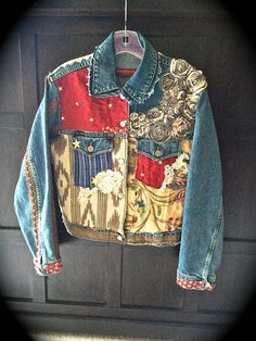 This collaged Jean Jacket started with a T shirt with an image of the wild horses, a canyon and calligraphy. Twinkle letters in the words WILD WEST. on the back. A bouquet of tea colored rag roses flows from the front left and over the shoulder to the back. Various RUSTIC swatches of antique and vintage fabrics through out. The collar was separated at the seams and stitched back together with rough edges showing. LOTS of machine and HAND stitches,,RUSTIC edges to most everything!! Gol...