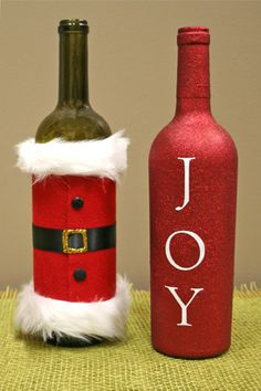 Dress up wine bottles for holiday parties! Felt, fur, buttons and a belt for Santa, Extreme spray glitter and vinyl letters for Joy!