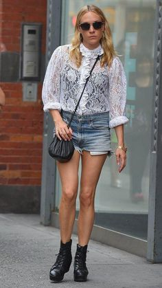 Chloë Sevigny wears a white lace top, denim cutoffs, a crossbody pouch bag and booties