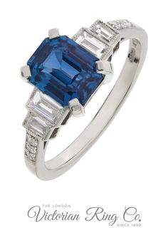 This Art Deco style sapphire engagement ring in platinum features a large emerald-cut sapphire with two baguette cut diamonds on either side. The band is set with a further six diamonds. Made in Hatton Garden by master jewellers to original 1930s designs.#hattongarden #madebyhand #bluesapphire #sapphireengagementring #sapphirering #baguettediamonds #londonvictorianringco #emeraldcutsapphire