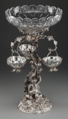 An English Victorian Silver-Plated Figural Epergne with Cut-Glass Bowls, circa 1880 -  22-1/4 inches high x 12-1/4 inches diameter (56.5 x 31.1 cm)  The epergne with a putti sitting on a domed, naturalistic textured base with grapevine-form standard issuing three scrolled arms, each with a hanging basket, the standard continuing to support a cut-glass bowl.