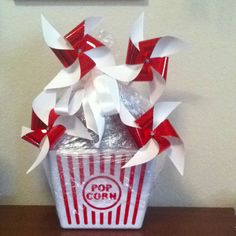 Gift basket- popcorn tub filled with drinks and popcorn..topped off with some homemade decorative pinwheels...I used Saran Wrap to secure it all together and tied it with a white ribbon