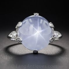 A shimmering white star (aka asterism) imbues this unusual and enchanting, light grayish-blue sapphire. The perfectly round cabochon weighs approximately 13 carats and is modestly presented in a handmade platinum mounting, circa 1930, enlivened with a sprinkling of tiny round diamonds. Both the side gallery and under gallery are ornamented with decorative piercing. An understated and sophisticated original Jazz Age jewel. Currently ring size 7.