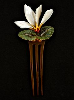 ART NOUVEAU CYCLAMEN HAIR COMB. France, Art Nouveau floral cyclamen comb. Gold, plique-à-jour and basse-taille enamel, mother-of-pearl, horn and rose cut diamonds. Signed Aucoc, circa 1900