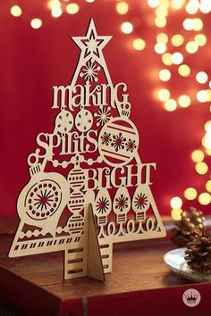 LASER-CUT CHRISTMAS TREE DECOR: Spruce up any mantel or shelf with this piece of elegant decor. The tree's intricate laser-cut design features holiday icons and a phrase that'll brighten anyone's spirit.