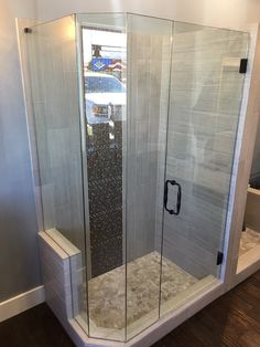 """We have various showers set up in our showroom for you to view.  This frameless enclosure display shows a door that swings in and out, 2 panels with mitered corners, and a notched return panel, 8"""" Victorian style handle, through 3/8"""" Clear Glass in Oil Rubbed Bronze finish"""