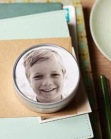 Here, a black-and-white photograph was added to a small metal tin with a glass lid (available at crafts stores in assorted sizes). Round tins can also function as magnets. To make the tins, print black-and-white photos onto ink-jet paper. Center lid on photo, and trace with pencil. Using scissors, cut along the inside of the traced line. Place photo in lid,  tape it to the lid's inner rim. To magnetize, glue a magnet to the bottom of an empty container.