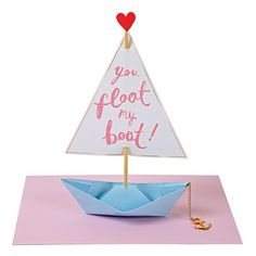 Tell your Valentine that they float your boat with this beautiful origami boat Valentine's card complete with sail topped with a love heart. The boat has a gold chain and anchor. The card comes with a