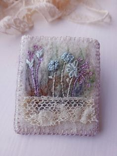 Antique Lace Embroidered Meadow Felt Brooch A small neat brooch embroidered on 3mm artisan felt, so wonderful to stitch on. First I needle felted a light background of mixed felt fibers. Then added tiny hand embroidered stitched flowers to make up this meadow scene in light shades (pale blue and lilac) A small piece of Edwardian lace (c1910) at end adds a tough of history. Wildly vintage little brooch, for lovers of stitch and lace !!!! Nice on a coat or jacket or pretty at top button of…