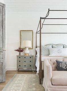 A beautifully distressed door leads to the master bedroom, where a graceful canopy bed makes the most of the soaring ceiling. Photo by Julie Soefer. Design Room, Home Bedroom, Bedroom Decor, Master Bedrooms, Bedroom Furniture, Bedroom Mirrors, Canopy Bedroom, Luxury Bedrooms, Bedroom Lighting