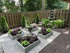A container garden can even consist of smaller raised planting boxes. This garden is made low-maintenance by removing grass in favor of mulch and pebbles, with a few small planting beds for color.
