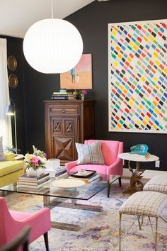 Colorful art, dark painted walls, pink chairs and eclectic furniture in a bold living room.