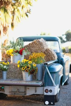 Pick-up loaded with hay bales, & buckets of flowers