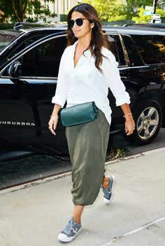 Camila Alves wears a white button-down shirt with loose cargo pants, a green leather waist bag, gray sneakers, and black sunglasses
