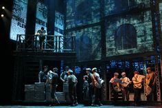 """The lighting in this scene from """"Newsies"""" is mostly blue and low intensity, except for the warm light on the four boys on stage left. They are the main focus in this scene and it is obvious from the warm highlight on them. In a strange way, the blue lighting in this scene makes me feel cold and it almost makes me feel like I'm touching steel. I think this could be reflective of the working class and how the news boys are pushing against that."""
