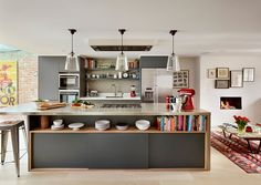 Dashing kitchen island in gray with open shelving and sleek stainless steel countertop [From: Roundhouse]