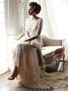 Maggie Sottero - VERINA, A dramatic illusion lace back and illusion sleeves adorn this hand-embellished sheath gown, glimmering with metallic lace appliqués and embroidered with beading drifting from shoulder to floor-skimming hem. A delicate scalloped hemline completes the look. Finished with pearl button over zipper back closure.