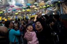 A man and his daughter pose for photos next to an installation of paper umbrellas -- symbols of the pro-democracy protests -- in the Causeway Bay district of Hong Kong on December 14, 2014.