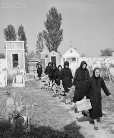 1955 The black clad widows of Goro, Italy, file into the village cemetery carrying benches to sit on while they talk to the graves of their dead husbands. Following and old custom, the widows come every Thursday and Sunday to pray beside the graves and keep company with the dead.    #TuscanyAgriturismoGiratola