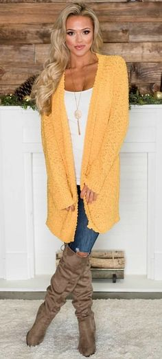 #winter #outfits yellow open cardigan, blue denim jeans, and brown knee-high botos