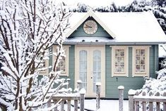 Mint green cozy cottage covered in snow