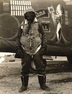 An airgunner stands before his B-24 bomber wearing what it took to survive at 25,000ft altitude, 1944