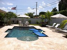 Florida backyard Custom designed turquoise pool w travertine deck