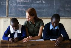 Two students sitting with teacher reading in classroom, Kenya