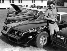 State Trooper stands beside police cars in Tallahassee, Florida, 1983. (State Archives of Florida) HUMANOID HISTORY: Photo