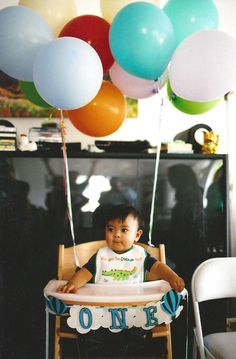 toddler in high chair with balloons photo
