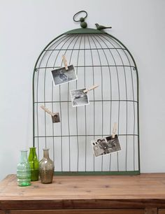 Add style and atmosphere with this ornate and unique Bird Cage Memo board in grey/green metal.  This lovely piece offers the perfect focal point to keep photos and invitations together in one place.  Designed to look like an old fashioned bird cage, complete with sweet little bird  pegs this quirky memo board  will instantly add interest to a plain wall.
