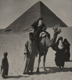 Egypt, MAYNARD OWEN WILLIAMS/National Geographic Creative. A family and a camel travel through the desert in front of a pyramid.