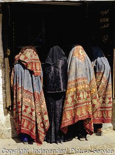 Four Yemeni women wearing colorful traditional abayas (cloaks) in the Old City of Sana'a, Yemen