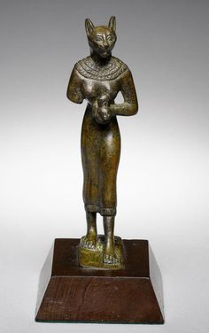 An Egyptian bronze figure of Bastet   Late Period, circa 664-332 B.C.  The cat-headed goddess shown striding forward, wearing the broad collar and a long tight dress, holding a lion-headed aegis to her chest in her left hand, 6in (15cm) high,