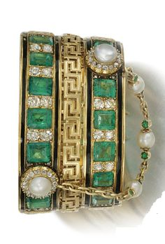 GOLD, ENAMEL, EMERALD AND DIAMOND BANGLE, 1860s. Designed as a wide band of step-cut emeralds alternating with circular- cut and rose diamonds within black enamel lines and Greek key motifs, clusters centring on a button pearl within a surround of circular-cut diamonds, to a similarly set fetter link chain connection, inner circumference approximately 164mm, French assay and maker's marks.