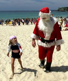 Santa on beach in New Zealand - it's summer Down Under Christmas-time and New Year!
