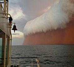White shelf cloud caps dust storm over ocean near Onslow Australia