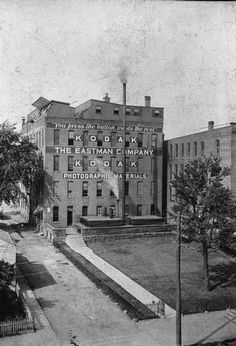The famous Kodak slogan, You Press the Button, We Do the Rest appears on George Eastmans original factory building on State Street, trumpeting the simplicity of using his Kodak camera. Mr. Eastman created the word Kodak, with a goal for the name to be easily pronounced in all languages. The photo is circa 1888.