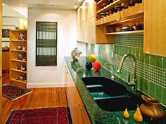 A green tile backsplash gives a vibrant, energized feel to this kitchen. In an ingenious, space-saving move, multiple wine racks were built into the cabinets above the sink.