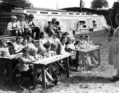 5th July 1933: Due to the warm weather the children of bargers who attend their own barge school at West Drayton have their lessons outdoors on the canal bank.