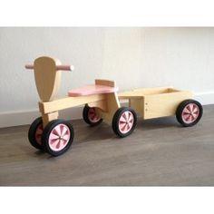 Mooie houten loopfiets en aanhanger van het merk New Classic Toys in de kleur roze met blank hout.