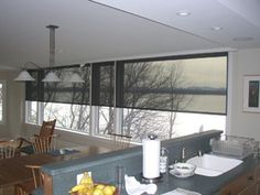 Solar screens control the harsh winter light through the kitchen windows in this home on the water, see next pic for full extension