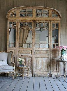 Mirrored windows in a huge doorframe as decor...just wonderful!