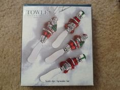 Santa Spreader Set of 4, (2 each of 2 designs),  by Towle Silversmiths, Silver Plated. Set has silver-plated Santas with red and green accents. 1) Santa is upright holding small Cmas tree in left hand, (2 each); 2) Santa appears to be lying down w/ hands/arms over head (attached to blade here). Has present w/ green ribbon at his feet which is the top of spreader.